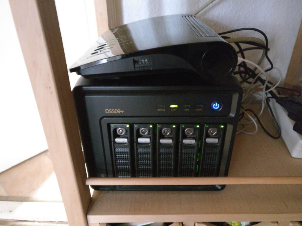Synology Diskstation DS509+ im Betrieb, darauf steht eine Fritz!Box 7590