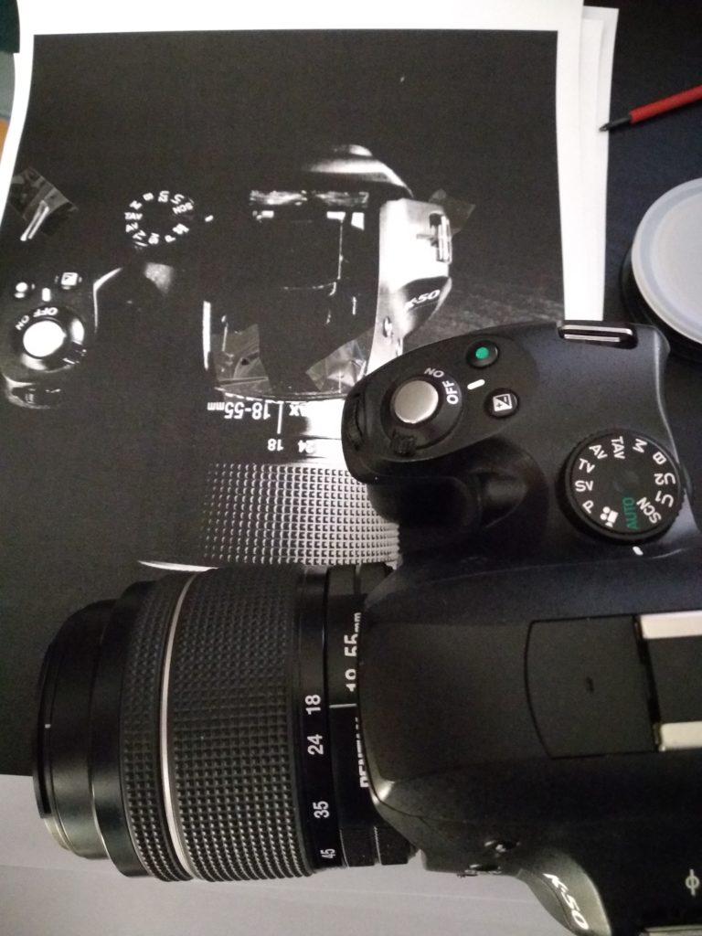 Pentax K-50 steht auf einem Foto-Ausdruck, die Schrauben sind an den entsprechenden Stellen auf dem Ausdruck festgeklebt.