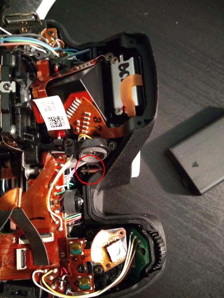 Das Obergehäuse ist entfernt, der Blick auf die Platinen ist frei. Innen in Objektivnähe, unter dem Mikrofon befindet sich die Spule mit dem festgeklemmten Anker.