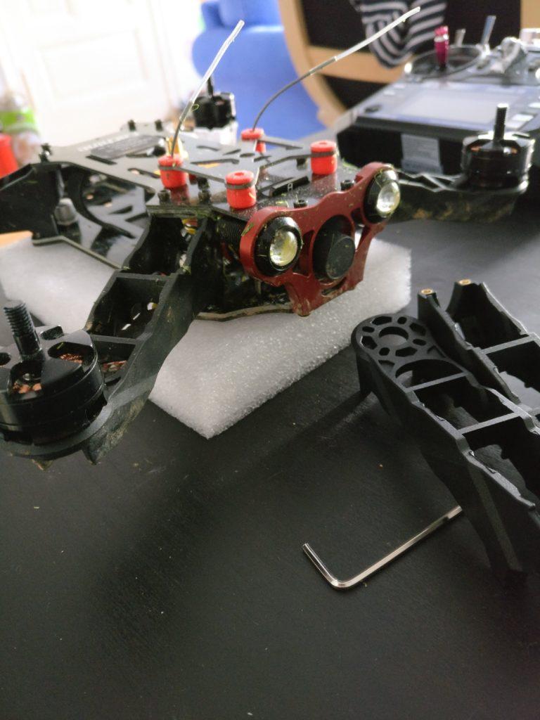 Die mit Grasschnitt verdreckte Drohne liegt auf einem Tisch, bei den beiden vorderen Beinen fehlen Teile der Füße. Vor der Drohne liegen zwei neue Beine und ein Inbusschlüssel.