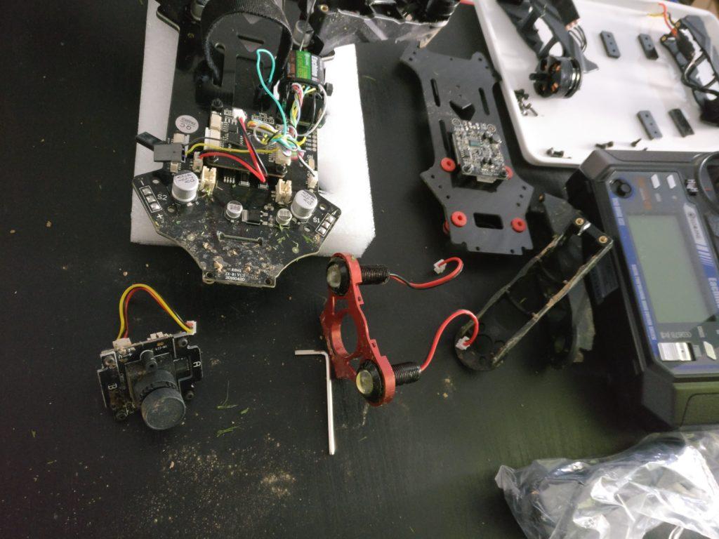 Ziemlich verdreckte Drohne liegt auf einem Tisch, die beiden vorderen Beine sind demontiert und die ESCs von der Platine abgelötet, das abgesteckte Kameramodul liegt vor der Drohne, die Sendeplatine ist noch an die demontierte obere Platte geschraubt.